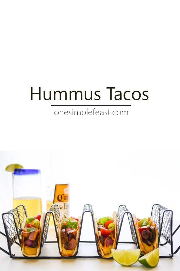 Loaded with roasted veggies like thick rings of sweet onion and mushrooms layered on top of garlicky hummus and melty cheddar, these Hummus Tacos are vegetarian taco perfection | onesimplefeast.com