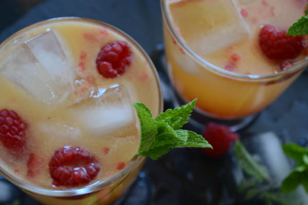 A delicious sweet tart Raspberry Mango Paloma cocktail, made with Trader Joes Mango Lemonade, fresh summer raspberries & Patron's Mango Citronage. | onesimplefeast.com